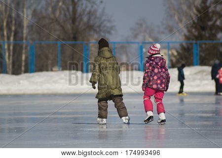 Two little girls on ice-rink - children's skating sport, rear view