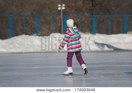 Winter sport - little girl on ice-rink - children's skating, telephoto