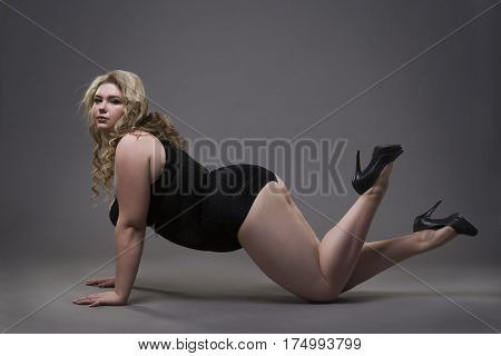 Young beautiful blonde plus size model in shapewear xxl woman in slimming underwear on gray studio background full length portrait