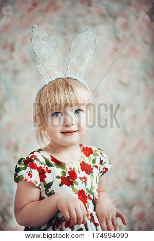 Fun Portrait of a cute happy little girl with bunny ears. Easter portrait. Floral background.