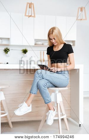 Vertical image of woman which sitting in kitchen and using tablet computer