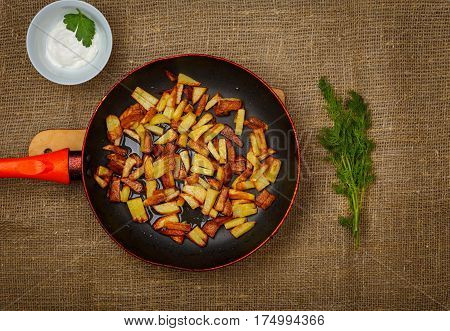 Frying pan with fried potatoes stand on the background of sackcloth. Bowl of sour cream and a bunch are nearby the frying pan