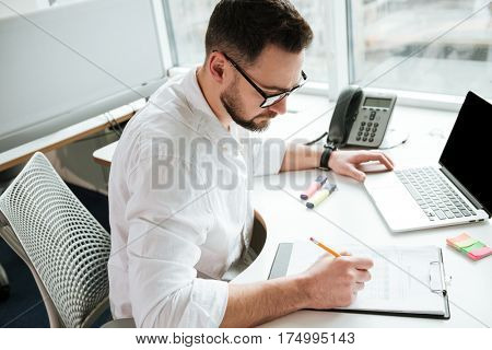 Top view of man in shirt and eyeglasses which writing something while sitting by the table with laptop computer