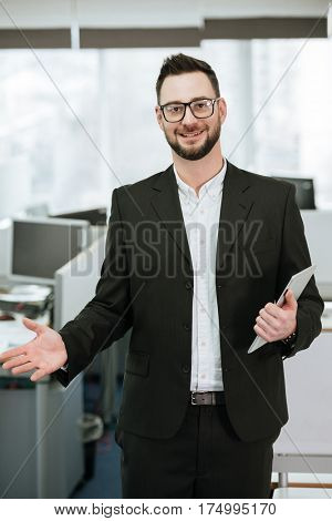 Vertical image of Bearded business man in suit and eyeglasses which holding tablet computer and looking at camera