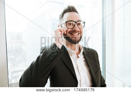 Smiling Bearded business man in suit and eyeglasses which talking on the phone with window on background
