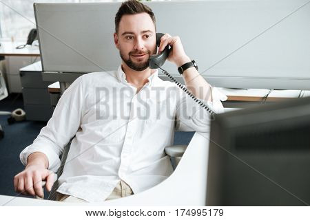 Bearded Man in shirt which sitting by the table and talking on phone