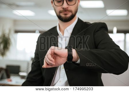 Cropped image of Bearded business man in suit and eyeglasses which looking at wristwatch
