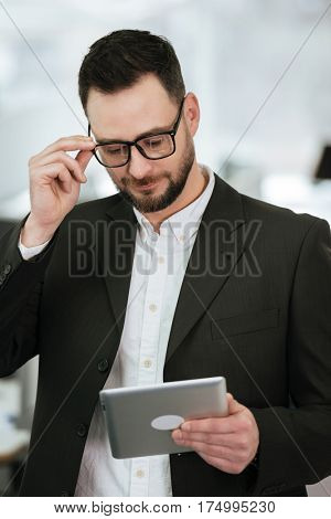 Vertical image of Pensive Bearded business man in suit and eyeglasses which using tablet computer in office