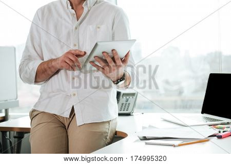 Cropped image of Man in white shirt which standing near the table and using tablet computer