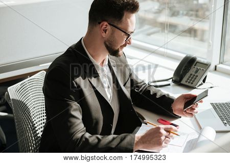Side view of Business man in suit and eyeglasses which sitting by the table and looking at smartphone