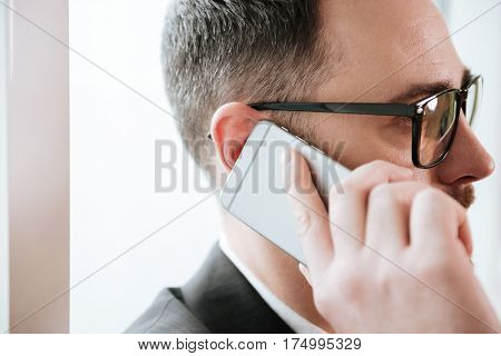 Close up portrait of Bearded business man in suit and eyeglasses which talking on phone. Side view
