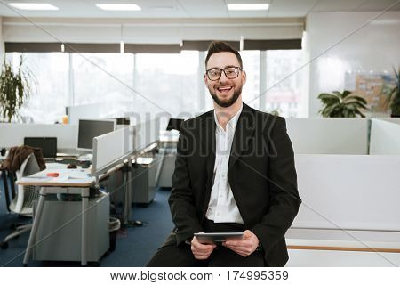 Bearded business man in eyeglasses and siut with tablet computer