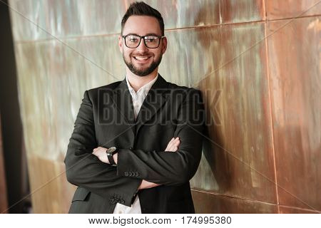 Smiling man in suit and eyeglasses which standing with crossed arms near the wall in office and looking at camera