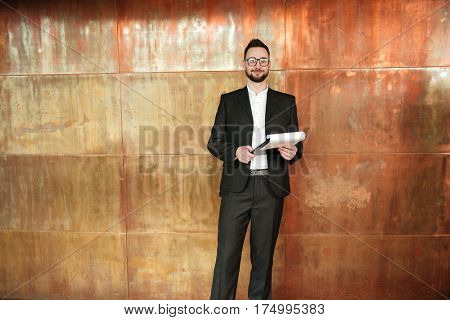 Smiling business man in suit and eyeglasses which standing near the wall in office with clipboard in hand and looking at camera