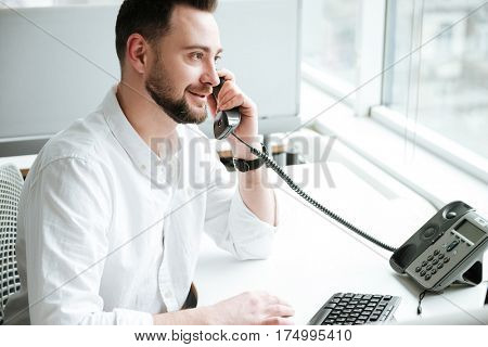 Side view of Man in shirt which sitting by the table and talking on phone