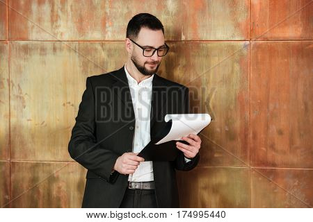 Business man in suit and eyeglasses which standing near the wall in office with clipboard in hands