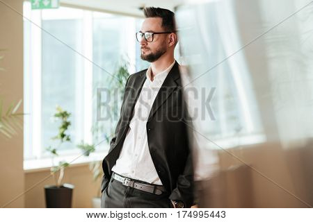 Cool Man in suit and eyeglasses which standing in office and looking away