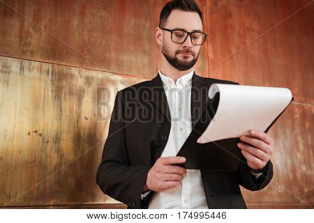 View from below of bearded business man in suit and eyeglasses which standing near the wall in office and looking at clipboard