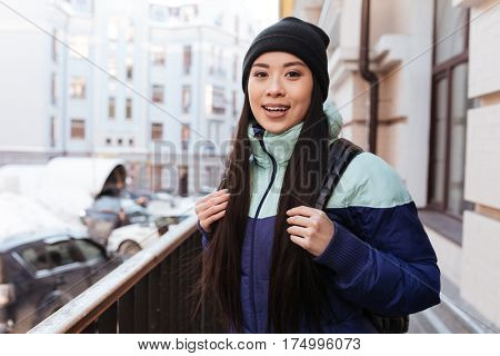 Happy Asian woman in warm clothes and with backpack which standing on the street and looking at camera
