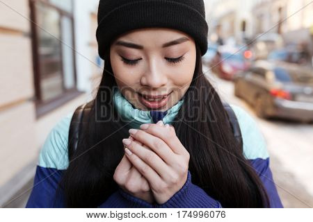 Smiling Frozen Asian woman in warm clothes which trying to keep warm on the street. Close up portrait