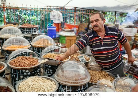 KEMER/ TURKEY - AUGUST 31, 2015. The seller of nuts in the Turkish market. Kemer, Turkey.