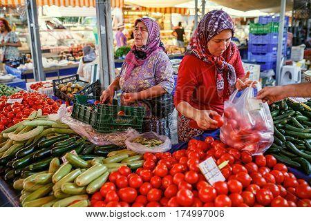 KEMER/ TURKEY - AUGUST 31, 2015. Muslim women selling the vegetables in the Turkish market. Kemer, Turkey.