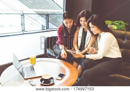 Three beautiful Asian girls using smartphone and laptop chatting on sofa at cafe modern lifestyle with gadget technology or working woman on casual business concept