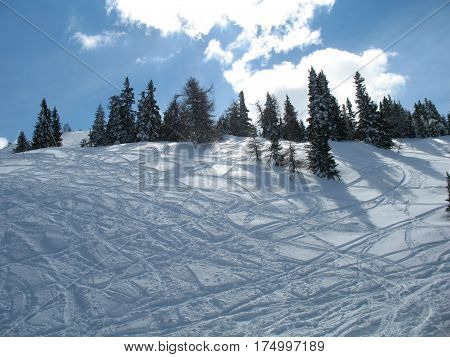 Mountain hill with fresh powder snow cut by the skiers and snowboarders. Top of mountain in winter.