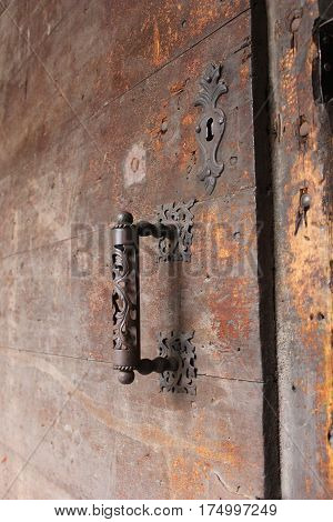 Vintage bronze rusted door handle on old wooden door with lock hole. Medieval ancient corrupted door with ornamented door handle and decorated lock hole.