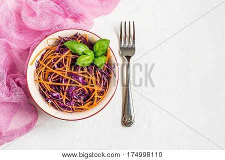 Fresh vitamin salad of red cabbage (scotch kale) with carrot and basil on white textured background. It is used in dietary and vegetarian food as well as for the prevention of cardiovascular diseases