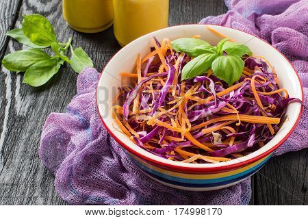 Fresh vitamin salad of red cabbage (scotch kale) with carrot and basil on a dark wooden background. It is used in dietary and vegetarian food. Selective focus