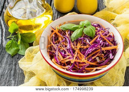 Fresh vitamin salad of red cabbage (scotch kale) with carrot and basil on a dark wooden background. It is used in dietary and vegetarian food as well as for the prevention of cardiovascular diseases