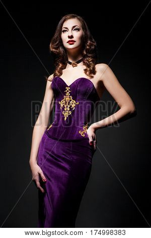 Beautiful young female wearing purple dress holding her waist. Vertical studio shot.