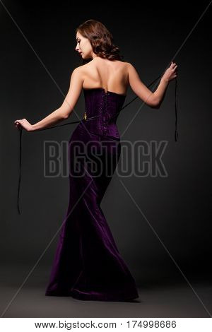 Back view of female wearing purple dress looking over shoulder.