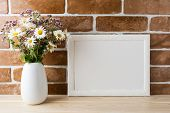White landscape frame mockup with wwildflowers bouquet in styled vase near exposed brick wall. Empty frame mock up for presentation design. Template framing for modern art. poster
