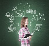 Portrait of a geek girl holding a black book and standing near a green chalkboard with an MBA sketch on it. poster
