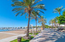 Sant Antoni de Portmany, Ibiza, November 6th, 2013.   Touring Ibiza in sunshine.   People walk along main boardwalk, now a stone concourse, beside the beach in Sant Antoni de Portmany, Ibiza, Spain.