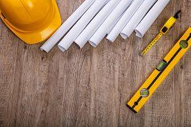 Tape measure, helmet and building level. Paper plans. Construction design. Wood rustic background.