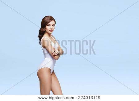 Fit And Sporty Girl In White Underwear. Beautiful And Healthy Woman Posing Over Cyan Background. Spo