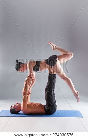 Young Couple Practicing Acro Yoga On Mat In Studio Together. Acroyoga. Couple Yoga. Partner Yoga.