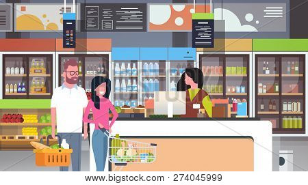 Retail Woman Cashier At Checkout Supermarket Couple Customers Holding Basket With Food Shopping Conc