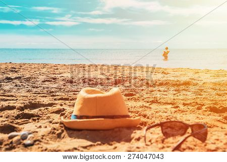 Hat And Glasses On The Sand On The Beach