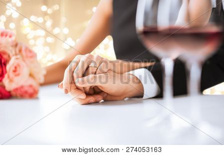 engagement, wedding and relationships concept - close up of engaged couple with diamond ring holding hands