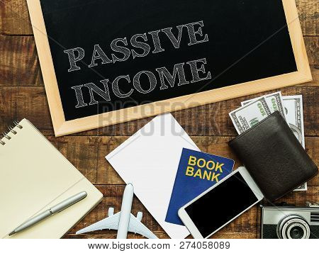 Passive Income, Financial Concept. Text Passive Income On Chalkboard At The Wooden Table With Book B