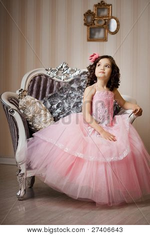 Een mooi meisje, een kind op een stoel in een mooie jurk