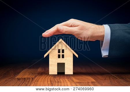 Property (family House) Insurance Protection Concept. Insurance Agent With Wooden Model Of The House