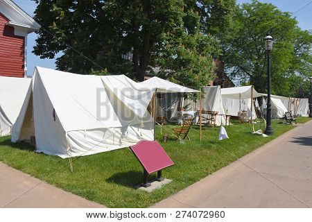 Civil War reenactment outdoor white tents set up on display outside in summer poster