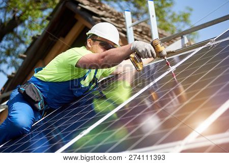 Professional technician installing shiny solar photo voltaic panel to metal platform using screwdriver. Exterior solar system installation, alternative renewable green energy generation concept. poster