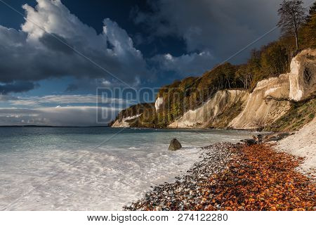 Chalk Cliffs On The Island Of Rügen In The National Park Jasmund. The Sun Illuminates The Chalk Clif