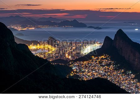View Of Favela Rocinha At Night With Ipanema District Behind, In Rio De Janeiro, Brazil